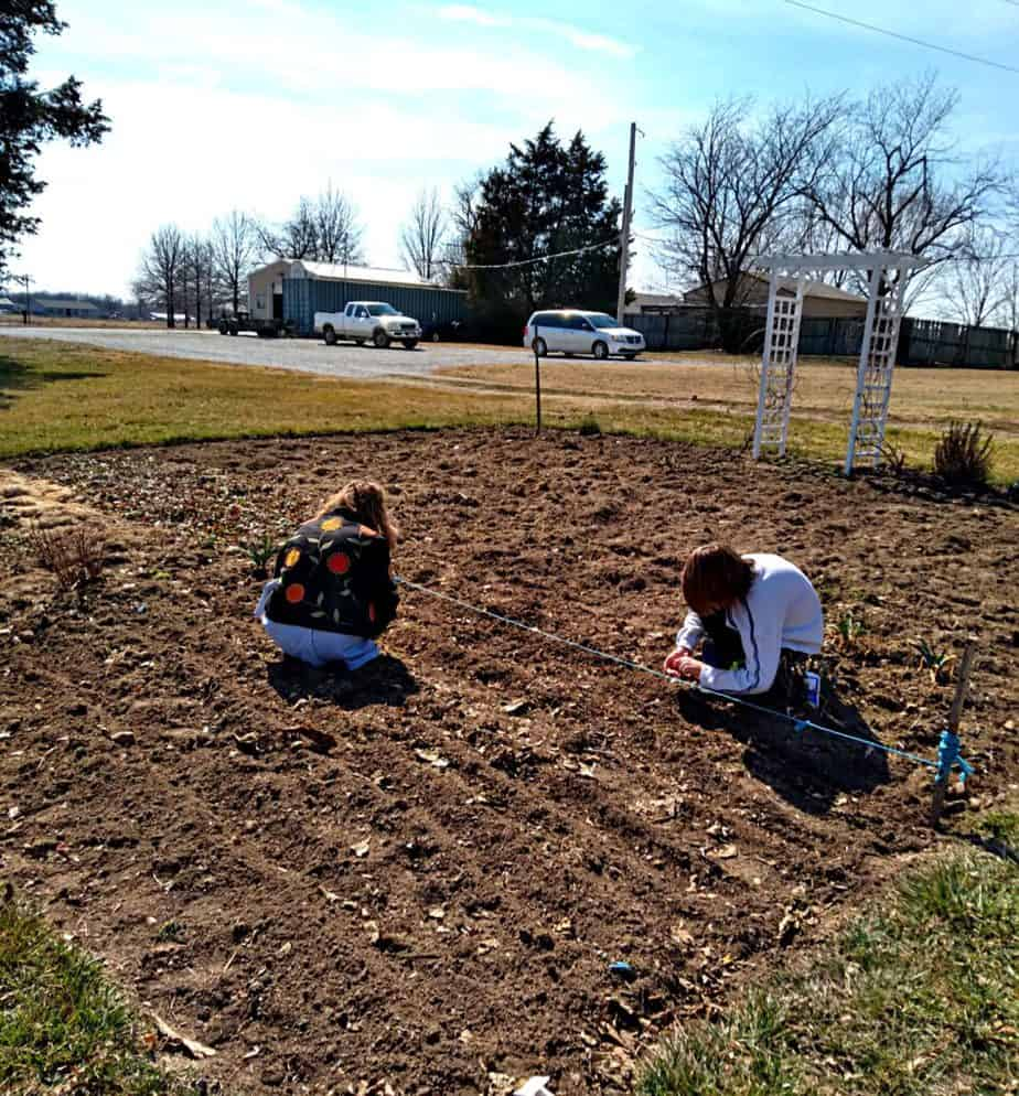 kids planting seeds in the garden with mom
